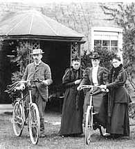 An old photograph of a family posing with bicycles