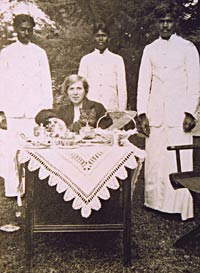 A woman at tiffin, surrounded by servants